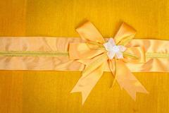 Abstract ribbon bow on fabric background. Stock Photos