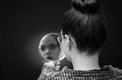 woman looking at self reflection in mirror..Stockfoto:. - stock photo