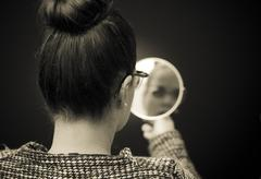 woman looking at self reflection in mirror - stock photo