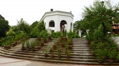 Wide staircase decorated with hibiscus bushes in pots, white pavilion on top Stock Footage