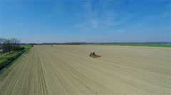Flying high above field with tractor loosening earth 4K - stock footage