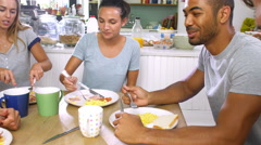 Stock Video Footage of Group Of Friends Eating Cooked Breakfast In Kitchen Together