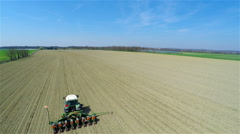 Flying close to tractor planting seeds on field 4K Stock Footage