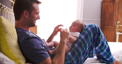 Father In Bed Playing With Newborn Baby Daughter Stock Footage