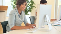 Young woman in office working on desktop computer - stock footage