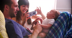 Parents In Bed Taking Photo Of Newborn Baby Daughter Stock Footage