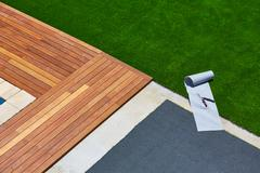 Artificial grass installation in deck garden with tools - stock photo