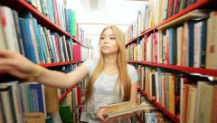 White girl in library between bookshelves Stock Footage