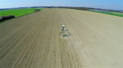 Flying behind a tractor loosening earth on big field 4K - stock footage