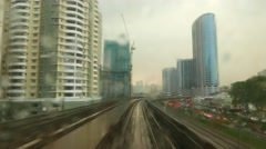 Rear view from moving LRT train, raindrops on window glass, dusk city Stock Footage
