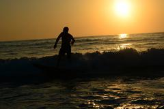 Silhouette of a person on a surfboard Stock Photos