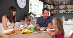 Family Eating Breakfast In Kitchen Together Stock Footage
