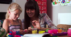 Mother And Daughter Playing With Modeling Clay In Bedroom Stock Footage