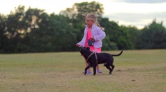 Little girl walks her dog in the park Stock Footage