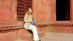 Woman sits and reads, Indian Architecture at The Agra Fort Stock Footage
