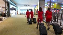 Air hostess in red suits run through duty free zone, hurry to flight boarding - stock footage