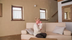Big living room with mother petting baby 4K Stock Footage