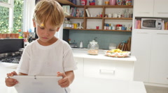 Son Playing In Kitchen Greeting Father Returning From Trip - stock footage