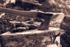 Vintage photo of an old axe and work gloves - stock photo