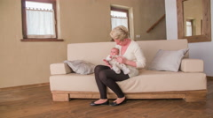 Stock Video Footage of Woman and newborn sit on sofa in living room 4K