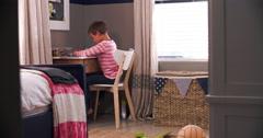 Boy Sitting At Desk In Bedroom Doing Homework Stock Footage
