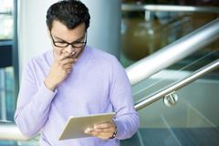 Closeup portrait, young captivated, absorbed, engrossed man in purple sweater - stock photo