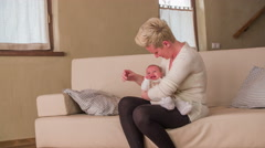 Mother and baby alone sit and talk on sofa in living room 4K Stock Footage