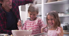 Father With Children Having Messy Fun Baking In Kitchen - stock footage