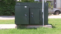 Green hydro power electrical transformer box on city street Stock Footage