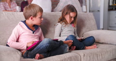 Children Use Digital Devices As Parents Talk In Background Stock Footage