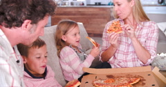 Family Sitting On Sofa Eating Takeaway Pizza Together Stock Footage