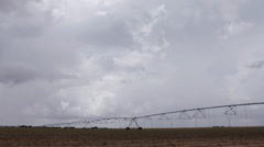 Storm clouds build and roil over an irrigation center pivot in the flat prairie  - stock footage