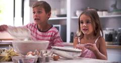 Slow Motion Shot Of Children Having Messy Fun In Kitchen - stock footage