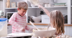 Slow Motion Shot Of Children Having Messy Fun In Kitchen - stock footage