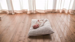 Cute baby resting on pillow on floor 4K Stock Footage