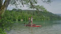 SLOW MOTION CLOSE UP: Young surfer couple SUPing along the lake land (part1) - stock footage