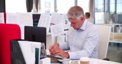 People Working At Desks In Modern Open Plan Office - stock footage