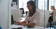 Businesswoman Working At Desk In Modern Open Plan Office Stock Footage