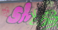 A mangled wire fence with urban graffiti in the background Stock Footage