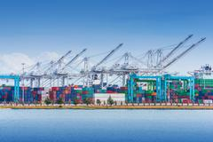 Cargo Seaport with Heavy Duty Lifts and Cargo Containers. Stock Photos