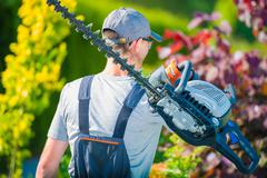 Professional Gardener with Large Gasoline Hedge Trimmer - stock photo
