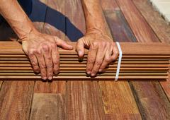 Ipe deck installation carpenter hands holding wood Stock Photos