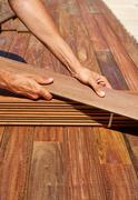 Ipe deck installation carpenter hands holding wood Stock Photos