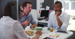Businessmen And Businesswoman Having Working Lunch In Office Stock Footage