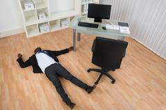 Unconscious Young African Businessman Lying On Floor In Office Stock Photos