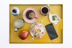 Smart Phone with Earbuds on Breakfast Tray - stock photo
