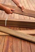 Ipe deck installation carpenter hands holding wood - stock photo