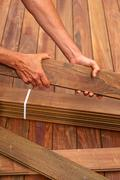 Ipe deck installation carpenter hands holding wood - stock photo