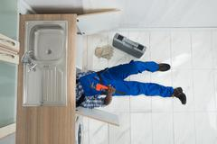 High Angle View Of Handyman Lying On Floor Repair Sink In Kitchen Stock Photos