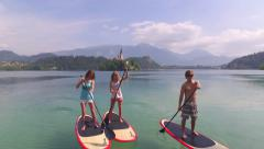 AERIAL: Young people SUP boarding towards the land on beautiful lake Bled Stock Footage